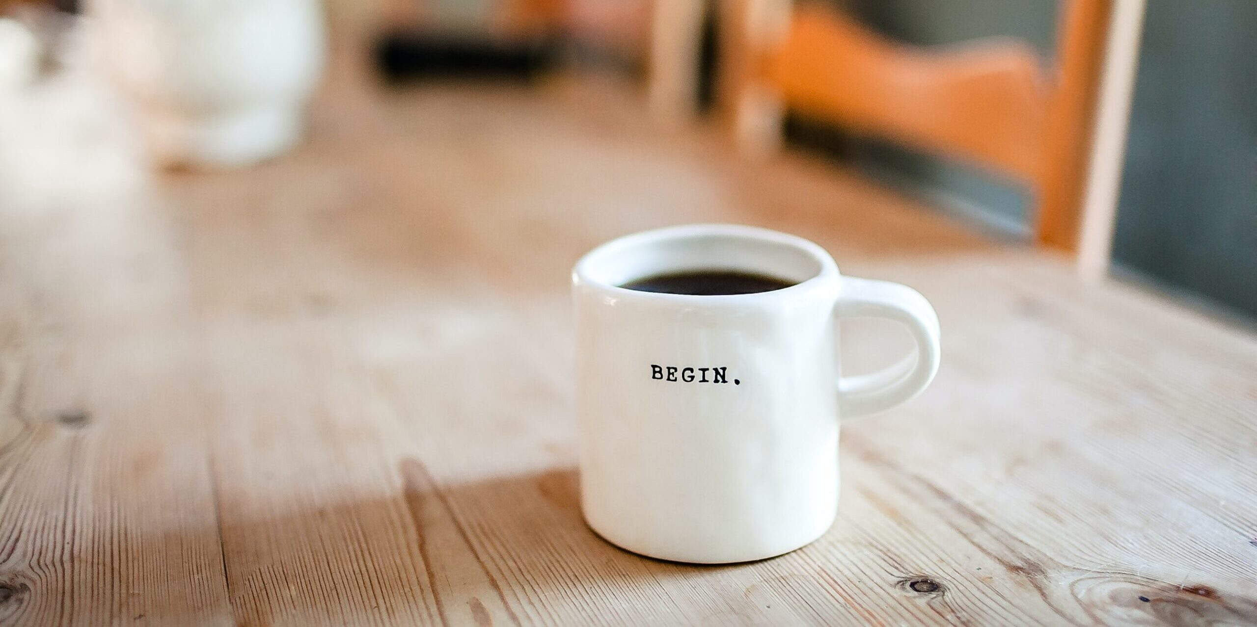 "coffee cup on a table with ""Begin."" on it"