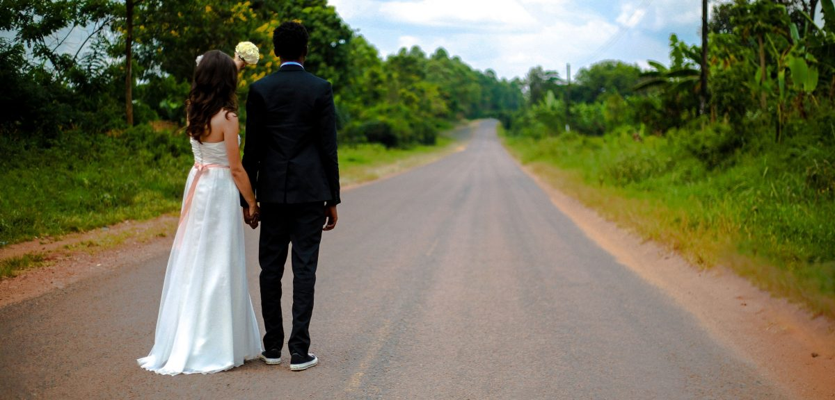 bride and groom standing in road